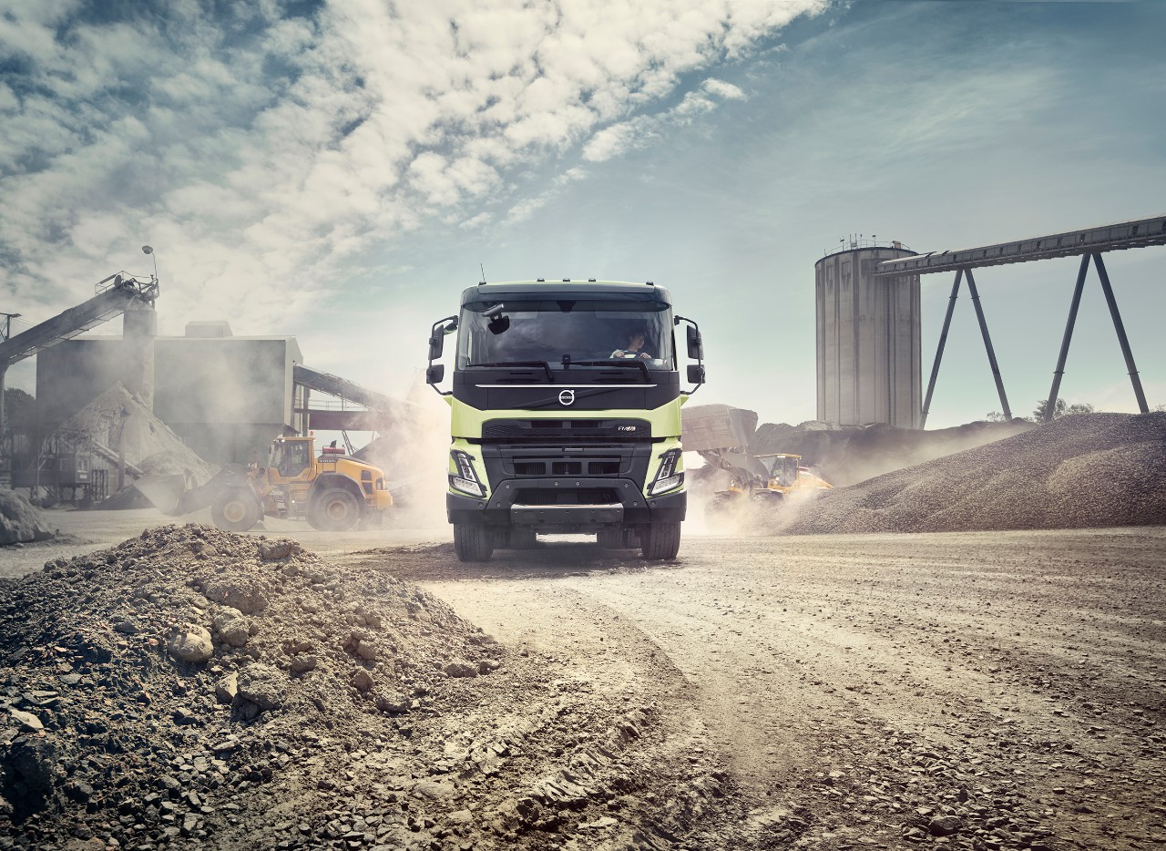 A Volvo FMX drives offroad through an industrial site