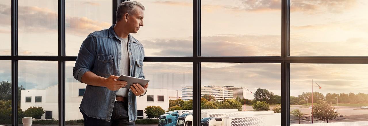 Een man met een tablet in zijn handen staat bij een raam en kijkt uit over zijn wagenpark