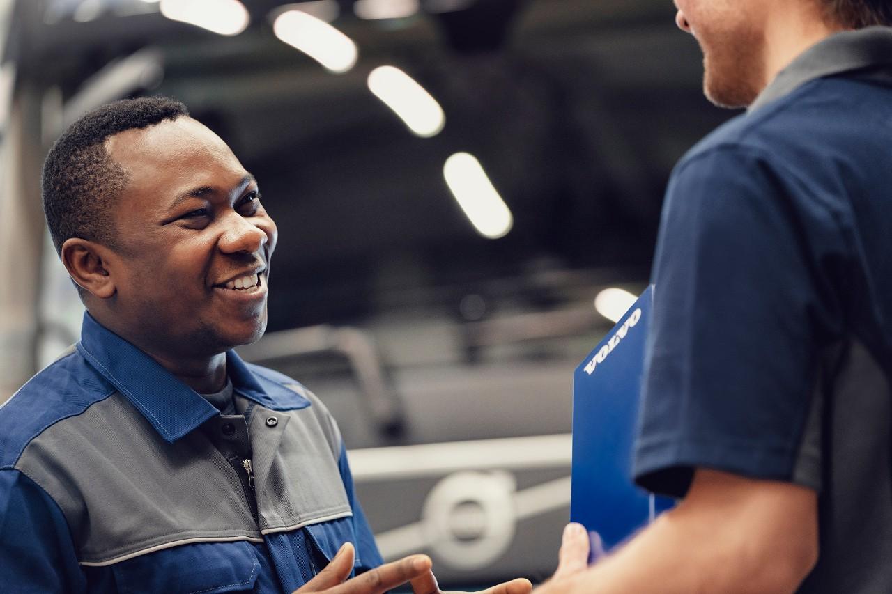 Een glimlachende Volvo-servicemonteur spreekt met een collega