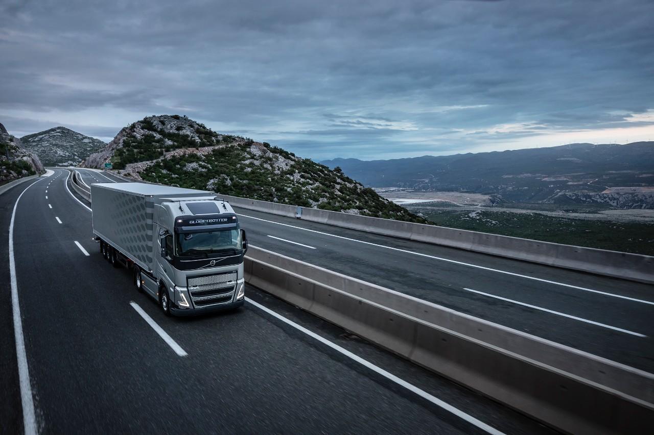 Een truck rijdt over een brug met bergen op de achtergrond