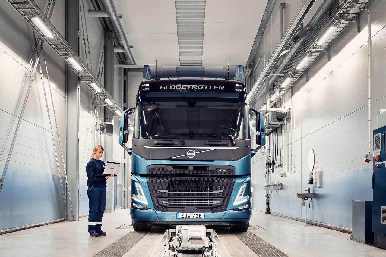 Een servicemonteur van Volvo met een laptop in haar hand staat naast een truck