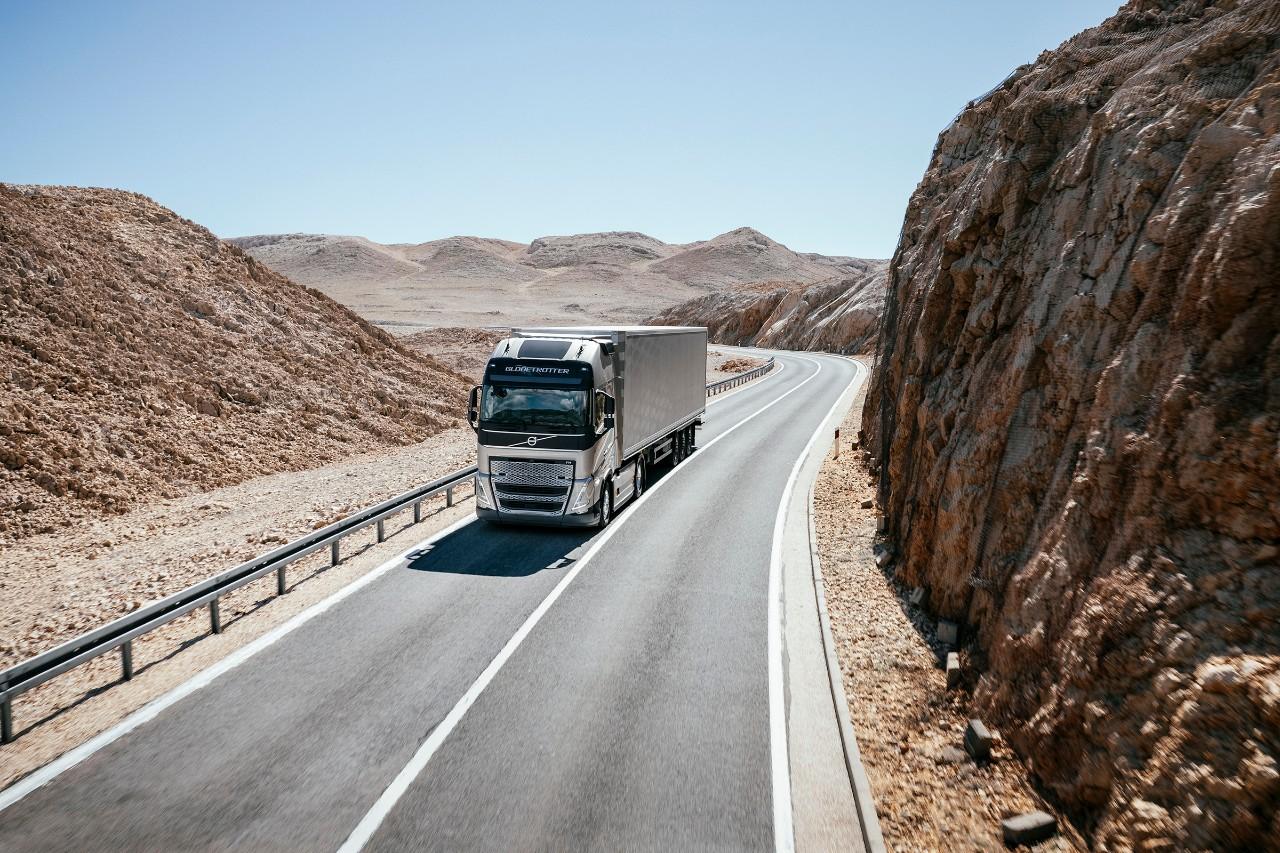 Een truck rijdt door een bergachtig woestijnlandschap